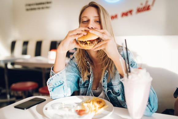 A young woman eating a hamburger, fries, and a shake inside a restaurant.