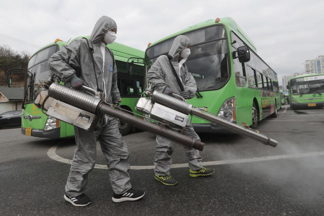 Workers wearing protective suits spray disinfectant as a precaution against the coronavirus at a bus garage in Seoul, South Korea. (AP)