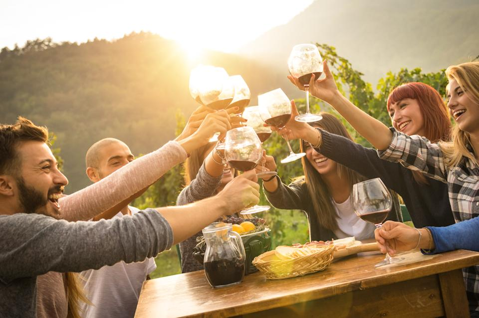 People toasting with wine glasses as the sun sets. A scene that might play out if you win Lotto.