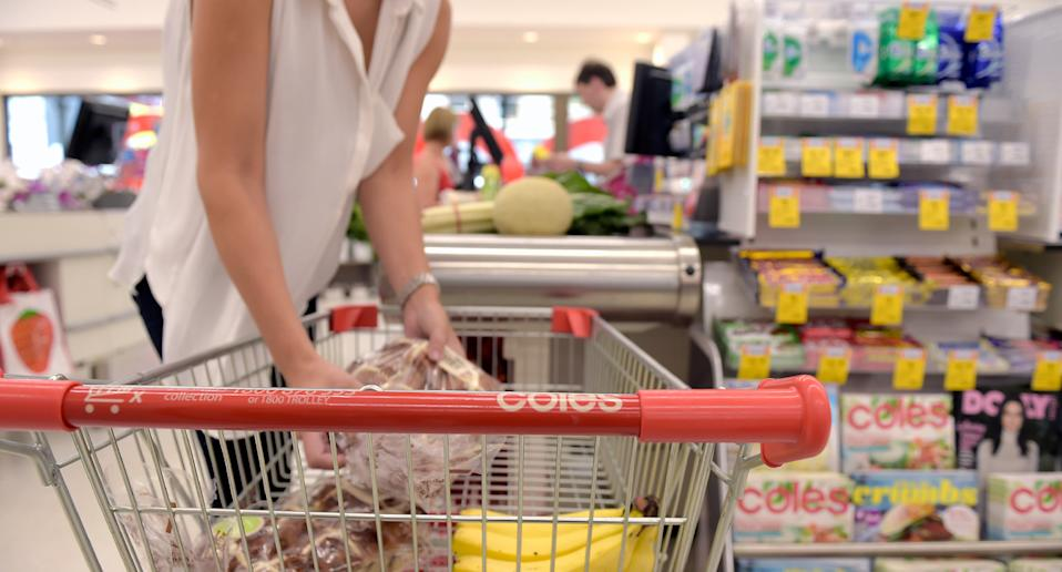 Woman shown unpacking her groceries inside Coles.