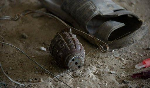 A granede lies on the floor next to a sandal inside the building where Taliban militants launched an attack in Kabul