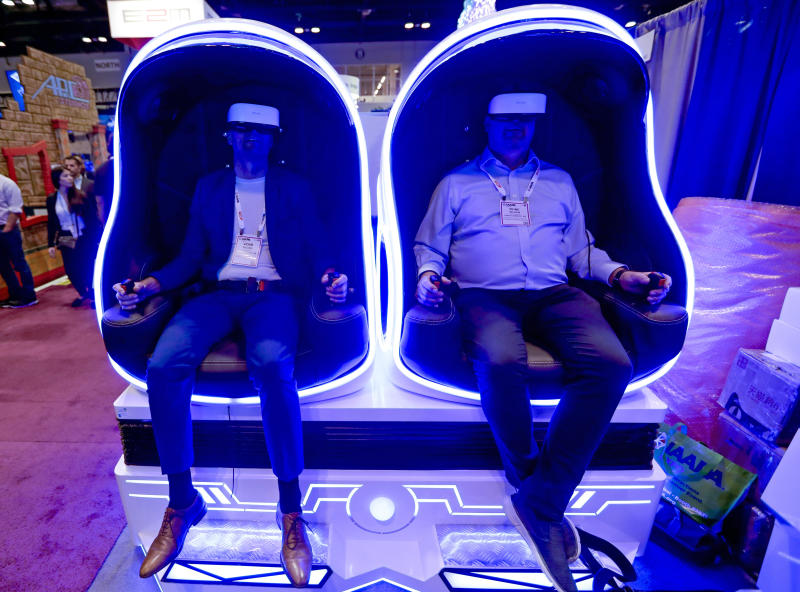 Attendees sample one of the many virtual reality rides during the International Association of Amusement Parks and Attractions convention Tuesday, Nov. 19, 2019, in Orlando, Fla. (AP Photo/John Raoux)