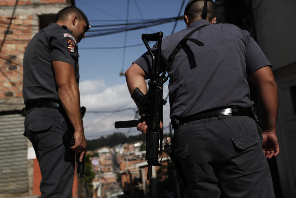 Police officers patrol in the Paraisopolis favela during a security operation in Sao Paulo November 6, 2012. The bloodshed has so far been concentrated in poorer areas and has not caused major disruptions to Sao Paulo's business community. It also has not approached the mayhem seen in 2006 when the PCC, as the crime group is known for its initials in Portuguese, effectively shut down activity in the metropolitan area of 20 million people for several days with orchestrated attacks that left nearly 200 dead.  Picture taken November 6, 2012.  REUTERS/Nacho Doce (BRAZIL - Tags: CRIME LAW POLITICS)