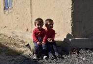Ademi and Alina, granddaughters of pensioner Rakya Kudaiberdiyeva, sit outside the family's rented house in Bishkek