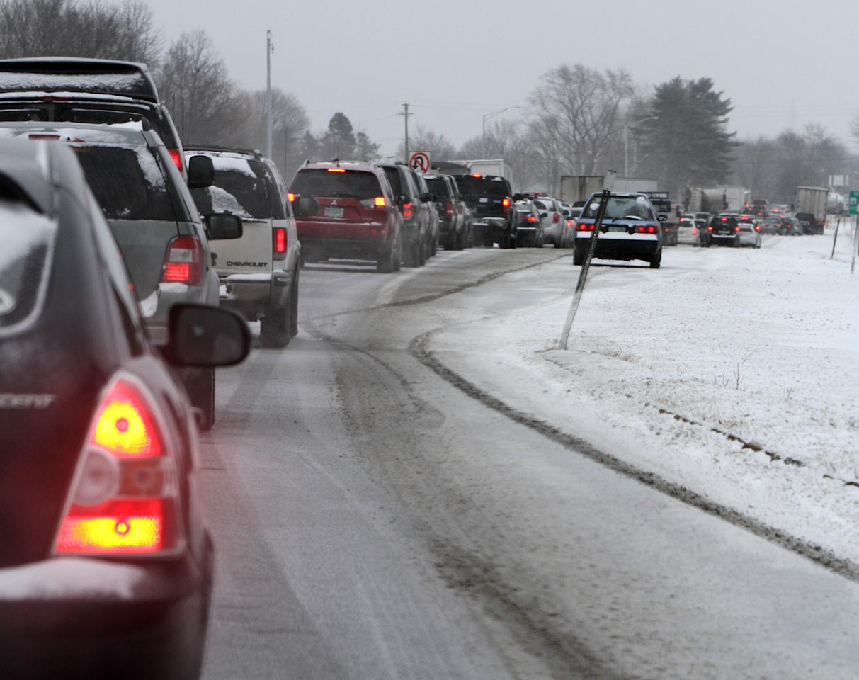 Cars are stuck in traffic as a winter storm arrives , Friday, Feb. 8, 2013 in Newington, N.H. Snow began to fall around the Northeast on Friday at the start of what's predicted to be a massive, possibly historic blizzard, and residents scurried to stock up on food and supplies ahead of the storm. (AP Photo/Jim Cole)