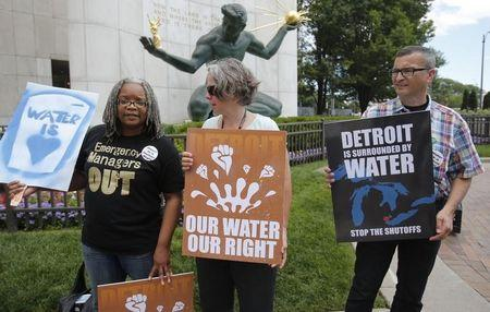 Detroit water activists Petty, Dziubek and Novak stand outside City Hall to protest against the increase in water shutoffs for residential customers with unpaid bills during a rally in Detroit