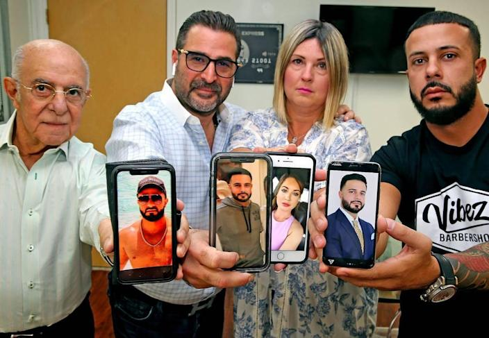Javier Perez's father Juan Perez, brother Luis Perez and brother Jorge Perez with Carolyn Alvarez's mother Liz Alvarez, all hold their phones with pictures of Carolyn and Javier, August 6, 2020. Javier Perez, a boat passenger was killed in the Bahamas along with his girlfriend Carolyn Alvarez. The family is lashing out at the boat captain, who they say left Perez and Alvarez to die in the waters off the islands.