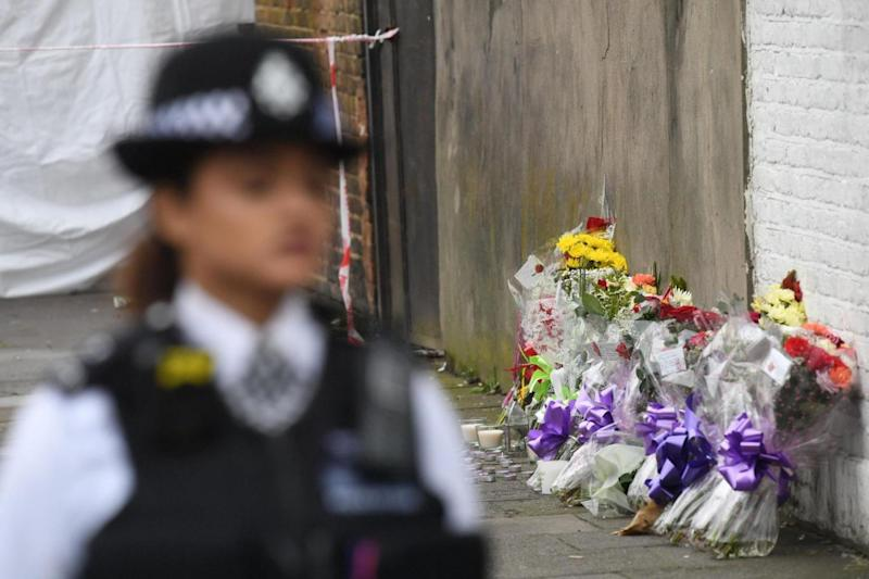 A police officer stands guard by floral tributes left at the scene of the fatal shooting in Tottenham (PA)