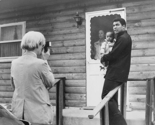 <p>Pop artist Andy Warhol, left, is shown photographing Muhammad Ali, his infant daughter, Hanna, and wife, Veronica, Thursday, August 18, 1977, at Ali's training camp in Deer Lake, Pa. (AP Photo)</p>
