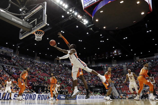 Auburn guard Jared Harper shoots as Clemson forward Elijah Thomas, obscured, defends during the first half of a second-round NCAA men's college basketball tournament game Sunday, March 18, 2018, in San Diego. (AP Photo/Gregory Bull)