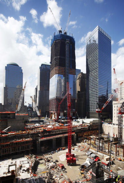 """In this April 25, 2011 file photo, work continues on """"One World Trade Center"""", center, in New York. More than a decade after 9/11, no one's quite sure what to call the spot that was once a smoldering graveyard but is now the site of the fast-rising, 1,776-foot skyscraper that will replace the twin towers. Some are calling the new skyscraper """"One World Trade Center,"""" but it's still """"ground zero"""" to others. (AP Photo/Mark Lennihan)"""