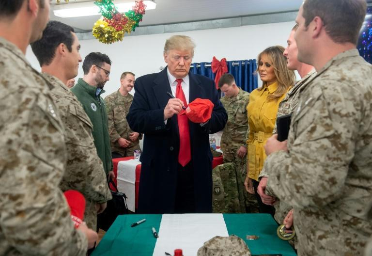 US President Donald Trump signs a hat as First Lady Melania Trump looks on while they greet members of the US military during an unannounced trip to Al-Asad Air Base in Iraq