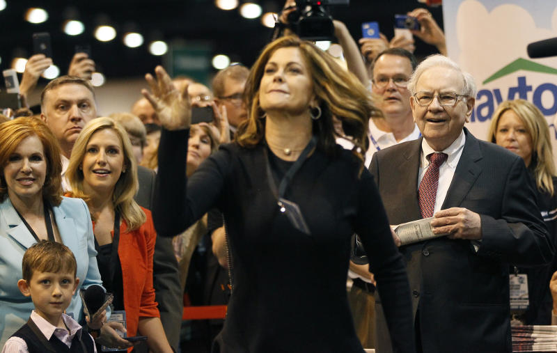 Berkshire Hathaway CEO Warren Buffett (R) watches as model Kathy Ireland throws a newspaper during a competition at a trade show, at the company's annual meeting in Omaha, Nebraska May 3, 2014. Warren Buffett's Berkshire Hathaway Inc on Friday said quarterly profit declined 4 percent, falling short of analyst forecasts, as earnings from insurance underwriting declined and bad weather disrupted shipping at its BNSF Railway unit. REUTERS/Rick Wilking(UNITED STATES - Tags: BUSINESS ENTERTAINMENT)