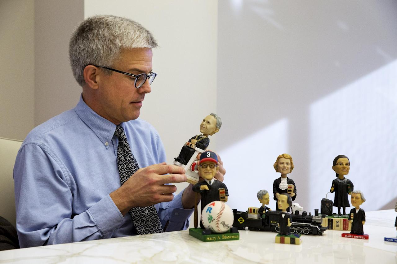 This photo taken Nov. 20, 2013 shows Ross Davies, professor of law and editor of The Green Bag, a law journal, holding one of the bobbleheads of Supreme Court justices he helped to design for The Green Bag, in Washington. They are some of the rarest bobblehead dolls ever produced. They're released erratically. They're given away for free, not sold. And if you get a certificate to claim one, you have to redeem it at a Washington, DC, law office.The limited edition bobbleheads of U.S. Supreme Court justices are the work of Davies, who has been creating them for the past ten years. When finished, they arrive unannounced on the real justices' desks, secreted there by unnamed confederates. And fans will go to some lengths to get one. (AP Photo/Jacquelyn Martin)