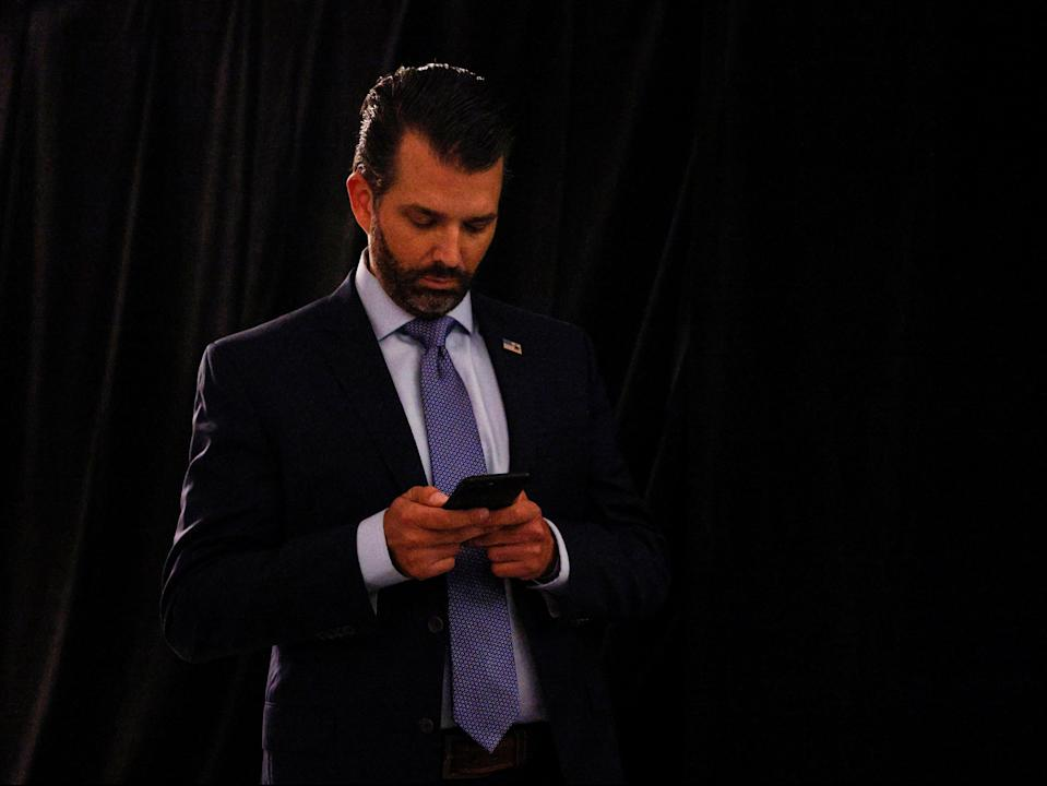 Donald Trump Jr uses his phone as he leaves after the first 2020 presidential campaign debate (REUTERS)
