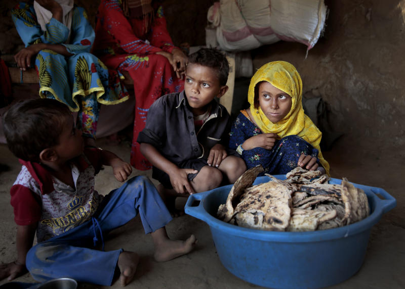 "FILE - In this Oct. 1, 2018 file photo, children sit in front of moldy bread in their shelter, in Aslam, Hajjah, Yemen. The U.N. children's agency says that millions of Yemeni children could be pushed to ""the brink of starvation"" as the coronavirus pandemic sweeps across the war-torn Arab country amid a huge drop in humanitarian aid funding. UNICEF on Friday, June 26, 2020 released a new report, ""Yemen five years on: Children, conflict and COVID-19."" (AP Photo/Hani Mohammed, File)"