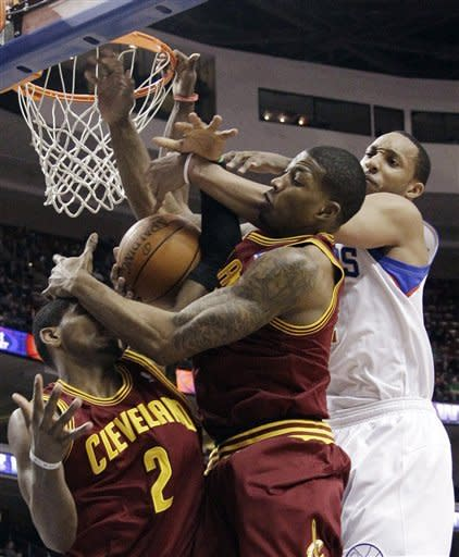 Cleveland Cavaliers' Kyrie Irving, left, and Alonzo Gee, center, struggle for a rebound with Philadelphia 76ers' Evan Turner, right, in the first half of an NBA basketball game, Tuesday, March 27, 2012, in Philadelphia. (AP Photo/Matt Slocum)