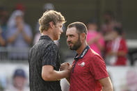 Cam Davis of Australia, left, shakes hands with Troy Merritt after winning in the fifth playoff hole in the final round of the Rocket Mortgage Classic golf tournament, Sunday, July 4, 2021, at the Detroit Golf Club in Detroit. (AP Photo/Carlos Osorio)