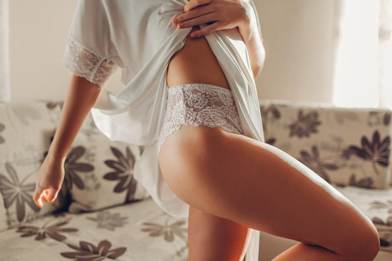 White high-waist panties on sportive booty. Slim woman wearing sexy lace underwear and dressing gown at home. Healthy young female body. Comfortable clothes