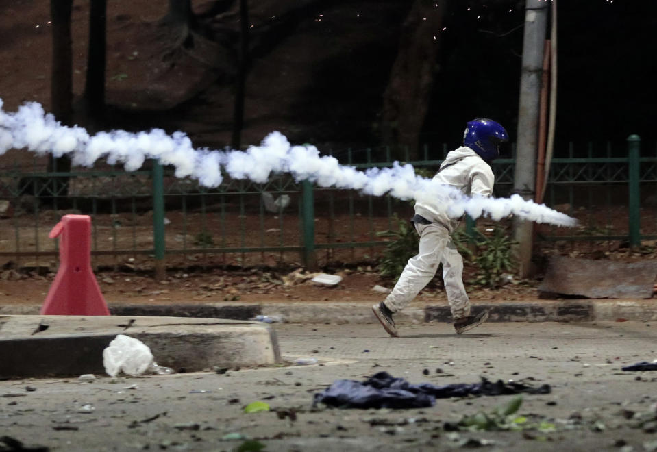 A protester runs away as a tear gas grenade flies past by during a clash in Jakarta, Indonesia, Monday, Sept. 30, 2019. Thousands of Indonesian students resumed protests on Monday against a new law they say has crippled the country's anti-corruption agency, with some clashing with police. (AP Photo/Dita Alangkara)