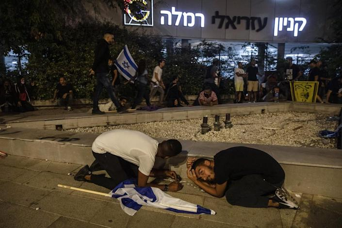 People, some bearing Israeli flags, stay low to the ground while others mill about during a rocket attack