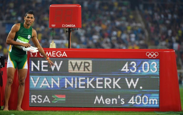 South Africa's Wayde van Niekerk poses by the results board after he broke the world record to win the 400m at the 2016 Olympic Games in Rio de Janeiro