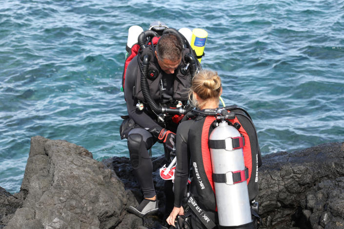 """FILE - In this Sept. 13, 2019, file photo, Greg Asner, left, director of the Center for Global Discovery and Conservation Science at Arizona State University, prepares to dive on a coral reef off the Big Island near Captain Cook, Hawaii. Flooding in March 2021 in Hawaii caused widespread and obvious damage, and the runoff from these increasingly severe storms is also threatening Hawaii's coral reefs. Although coral reefs worldwide face threats from global warming, including marine heatwaves that bleach and kill coral, storm runoff could prove a more serious and immediate threat to reefs in the state. """"In Hawaii, I would rate runoff much higher than marine heatwaves in driving coral decline,"""" said Asner. (AP Photo/Caleb Jones, File)"""