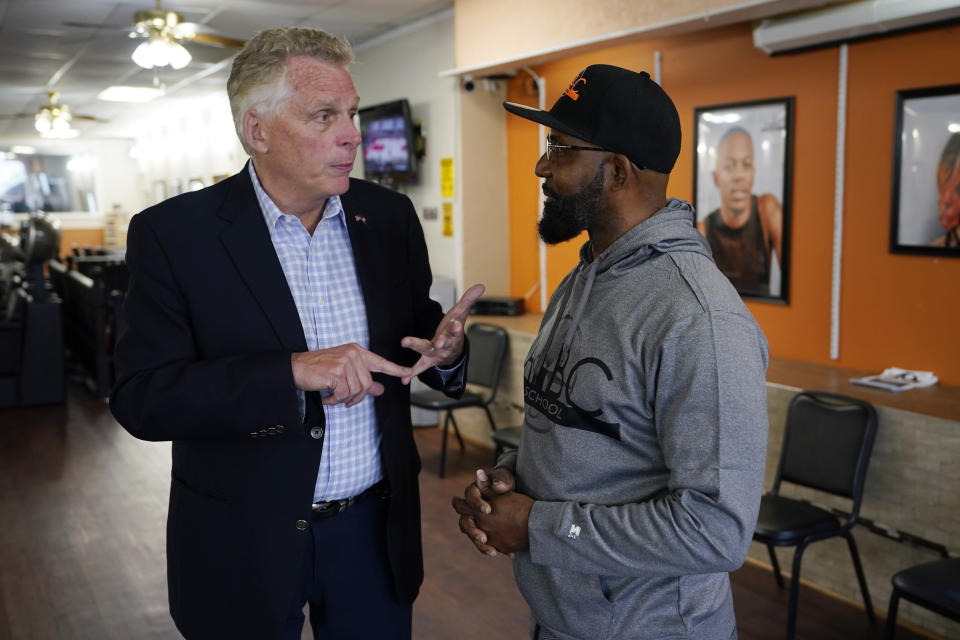 Democratic gubernatorial candidate, former Gov. Terry McAuliffe, left, talks with Wes Nicholas during a tour of downtown Petersburg, Va., Saturday, May 29, 2021. McAuliffe restored Nicholas's voting rights in 2015. McAuliffe faces four other Democrats in the a primary June 8. (AP Photo/Steve Helber)