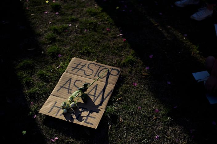 A sign is laid on the grass during a Stop Asian Hate rally in Houston on March 20, 2021.