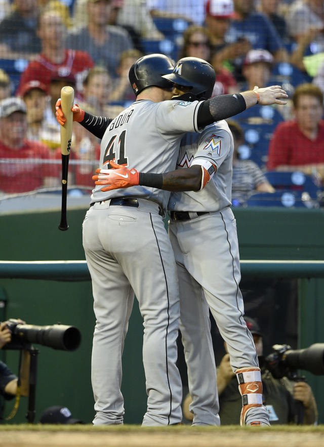 Miami Marlins' Justin Bour (41) hugs Cameron Maybin, right, after Bour hit a two-run home run during the fourth inning of a baseball game against the Washington Nationals, Thursday, July 5, 2018, in Washington. (AP Photo/Nick Wass)