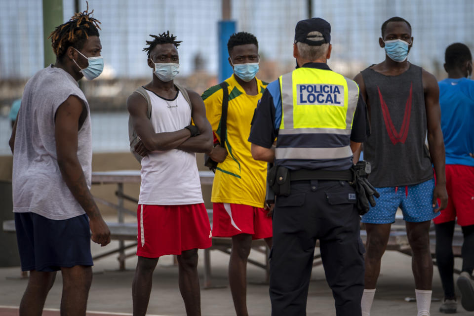 A police officer tells migrants and asylum-seekers to stop playing soccer due to coronavirus restrictions on contact sports in Gran Canaria island, Spain, Tuesday, Aug. 18, 2020. Migrants are increasingly crossing a treacherous part of the Atlantic Ocean to reach the Spanish archipelago near West Africa, in what has become one of the most dangerous routes to European territory. (AP Photo/Emilio Morenatti)