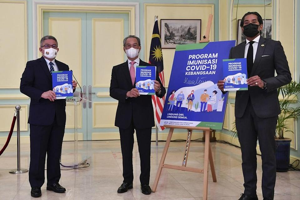 Prime Minister Tan Sri Muhyiddin Yassin (centre) at the launch of the National Covid-19 Immunisation Programme Handbook at the Perdana Putra Building in Putrajaya February 16, 2021. — Bernama pic
