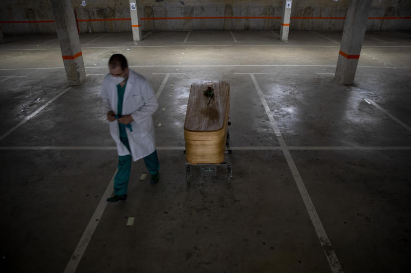Head mortician Jordi Fernandez, walks next to the coffin of the last COVID-19 victim stored at an underground parking garage that was turned into a morgue, at the Collserola funeral home in Barcelona, Spain Sunday May 17, 2020. A funeral home in Barcelona has closed a temporary morgue it had set up inside its parking garage to keep the victims of the Spanish city's coronavirus outbreak. The last coffin was removed and buried on Sunday. In 53 days of use, the temporary morgue has held more than 3,200 bodies. (AP Photo/Emilio Morenatti)