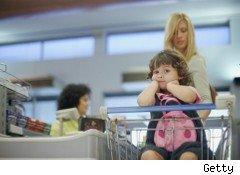Girl in supermarket  cart at grocery checkout