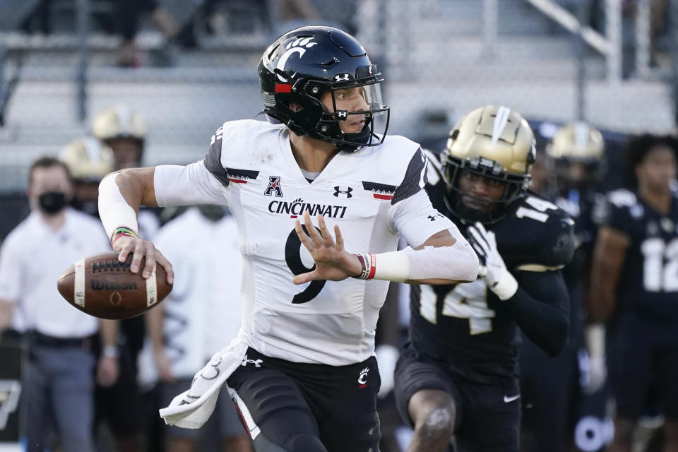 Cincinnati quarterback Desmond Ridder looks for a receiver as Central Florida defensive back Corey Thornton (14) pursues during the first half of an NCAA college football game, Saturday, Nov. 21, 2020, in Orlando, Fla. (AP Photo/John Raoux)