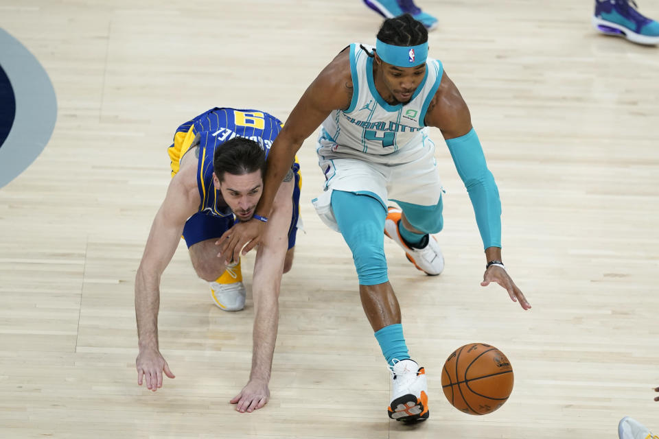 Charlotte Hornets' Devonte' Graham (4) and Indiana Pacers' T.J. McConnell (9) vie for a loose ball during the first half of an NBA basketball Eastern Conference play-in game Tuesday, May 18, 2021, in Indianapolis. (AP Photo/Darron Cummings)