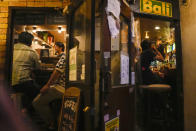 People gather at bars after government imposed 8 p.m. closing time for restaurants and bars under Tokyo's fourth state of emergency Saturday, July 17, 2021, in Tokyo. The latest state of emergency has asked restaurants and bars to close by 8 p.m., if not entirely. This has pushed people to drink outside, although many bars remain open and bustling with customers who are defying the rules and expressing frustration and indifference. (AP Photo/Kiichiro Sato)