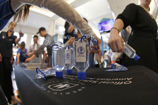 Fans reach for hand sanitizer before the start of the Denver Nuggets vs Dallas Mavericks NBA basketball game, Wednesday, March11, 2020, in Dallas. The Mavericks supplied the sanitizer for free. (AP Photo/Ron Jenkins)
