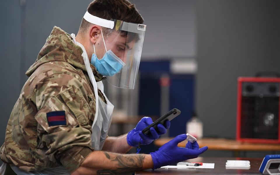 A British Army soldier, 1st battalion Coldstream Guards, records and processes tests at a coronavirus testing centre set up at the Merseyside Caribbean Council Community Centre in Liverpool, north west England, - Oli Scarff/AFP