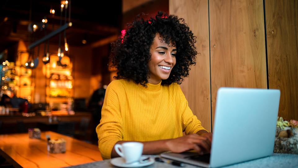 Beautiful smiling African American woman using laptop at the bar.