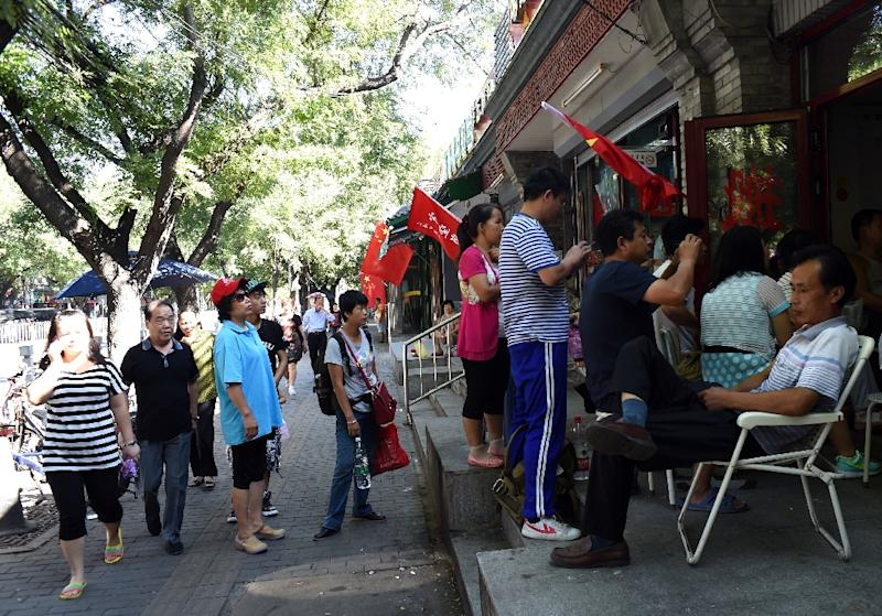 Residents gather outside a shop in Beijing on September 3, 2015 to watch a TV broadcast of the military parade from Tiananmen Square marking the 70th anniversary of victory over Japan and the end of World War II (AFP Photo/Goh Chai Hin)