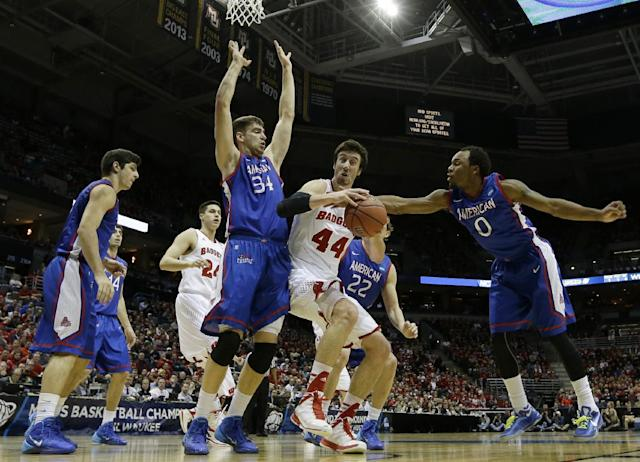 Wisconsin forward Frank Kaminsky (44) drives to the basket against American center Tony Wroblicky (34) and guard Darius Gardner (0) during the first half of a second-round game in the NCAA college basketball tournament Thursday, March 20, 2014, in Milwaukee. (AP Photo/Morry Gash)