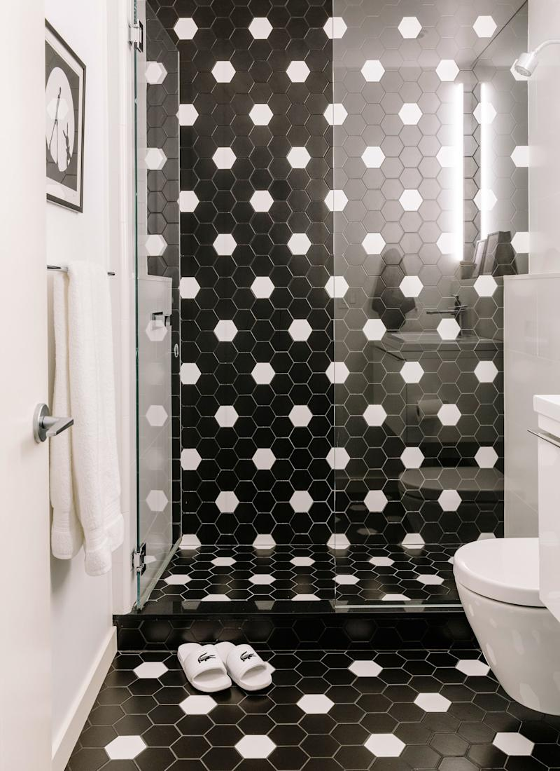 In the bathroom, Jessica and Sarah used basic black and white hexagon tiles to design a graphic pattern that runs from the floor to the ceiling.