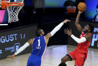 Toronto Raptors' Terence Davis, right, shoots against Philadelphia 76ers' Mike Scott during the second half of an NBA basketball game Wednesday, Aug. 12, 2020 in Lake Buena Vista, Fla. (AP Photo/Ashley Landis, Pool)