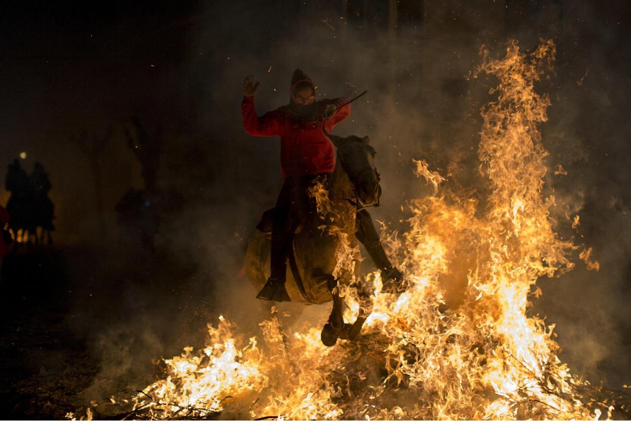 """A man rides a horse through a bonfire as part of a ritual in honor of Saint Anthony the Abbot, the patron saint of domestic animals, in San Bartolome de Pinares, about 100 km west of Madrid, Spain on Monday, Jan. 16, 2017. On the eve of Saint Anthony's Day, hundreds ride their horses through the narrow cobblestone streets of the small village of San Bartolome during the """"Luminarias,"""" a tradition that dates back 500 years and is meant to purify the animals with the smoke of the bonfires and protect them for the year to come. (AP Photo/Emilio Morenatti)"""