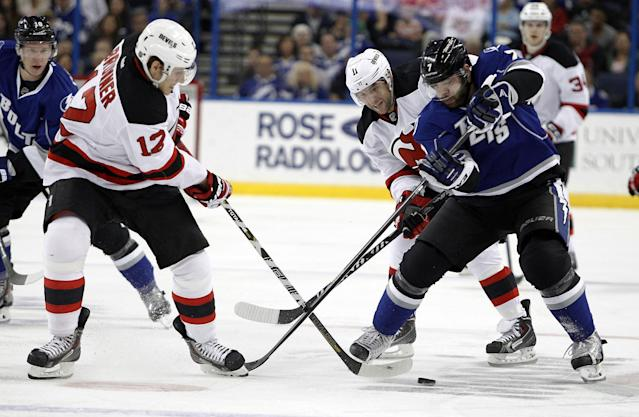 Tampa Bay Lightning defenseman Radko Gudas (7), of the Czech Republic, vies for the puck against New Jersey Devils right wing Damien Brunner (12), of Switzerland, and right wing Stephen Gionta (11) during the first period of an NHL hockey game Saturday, March 15, 2014, in Tampa, Fla. (AP Photo/Brian Blanco)
