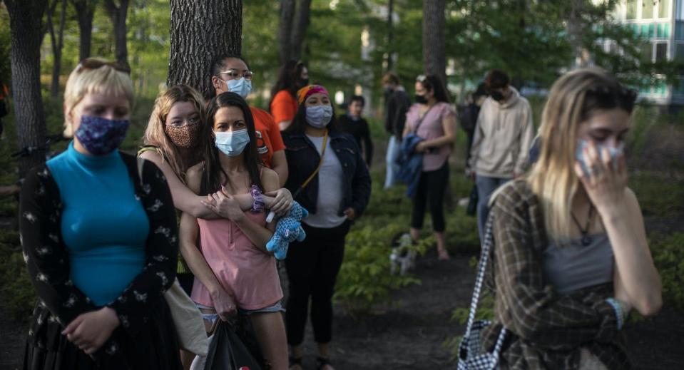 People stand outside at a memorial wearing face masks with a range of sad, stunned and exhausted emotion on their faces.