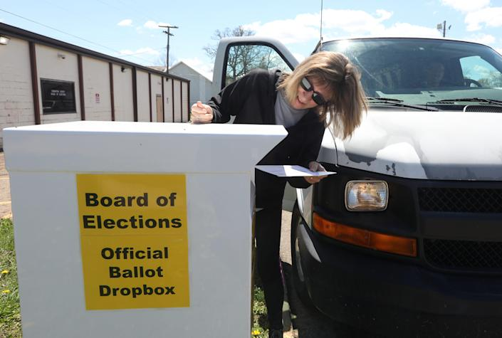 Cindy Massie puts her ballot in the drop box outside the Coshocton County Board of Elections.