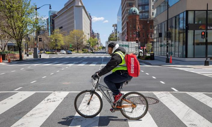 """<span class=""""element-image__caption"""">A Grubhub delivery person makes bicycle deliveries on the empty streets of Washington DC.</span> <span class=""""element-image__credit"""">Photograph: Erik S Lesser/EPA</span>"""