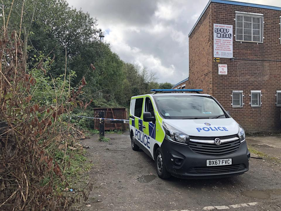 A police vehicle outside where West Midlands Police have cordoned off a pathway alongside industrial units Industrial Estate in Brierley Hill, West Midlands, in the area where two men were found shot dead in a car on Wednesday afternoon.